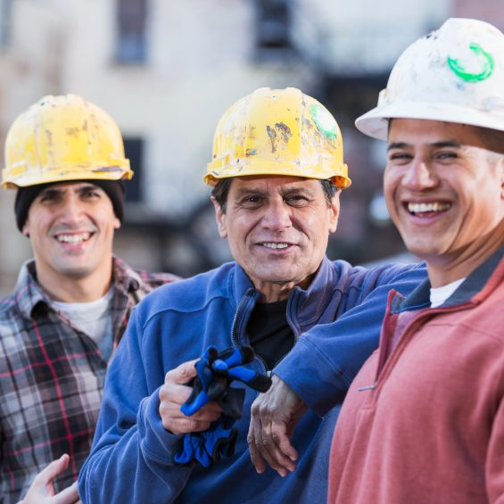 A group of three multi-ethnic men wearing white and yellow hard hats, standing in a row.  The focus is on the worker in the middle,  He is the foreman of this work crew, an Hispanic man in his 50s wearing a royal blue shirt, smiling and pointing at the camera.  They are construction workers, engineers or utility workers in the city, buildings out of focus behind them.